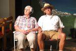 Emilia (M. Hornbogner) und Korbinian (H. Mummert) sitzen im Garten, während Nachbar Schmittke ein Sommerfest feiert. © OVTP / mib