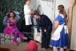 Alice gelangt in eine Küche, wo eine Grinsekatze sitzt, eine Köchin hauptsächlich mit Pfeffer kocht und ein Kind sich in ein Schweinchen verwandelt. © G. Prantl